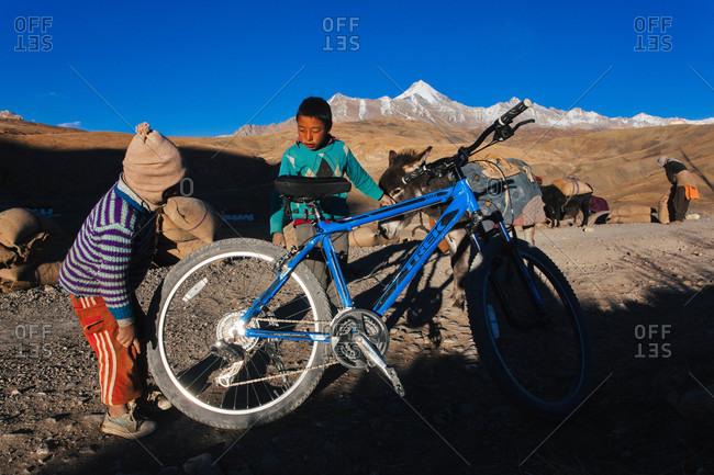Himachal Pradesh, India - October 19, 2013: Boys looking at a bicycle in Himachal Pradesh, India