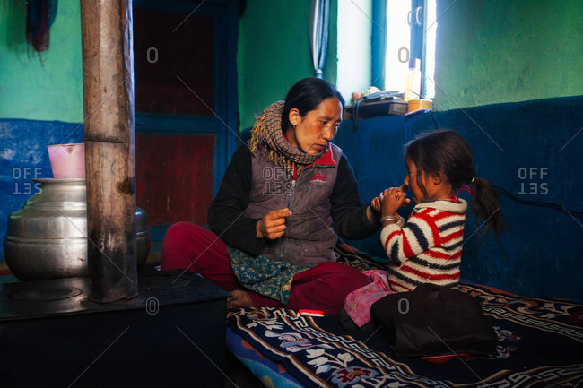 Himachal Pradesh, India - October 19, 2013: Mother and daughter in their kitchen in Langza village, Himachal Pradesh, India