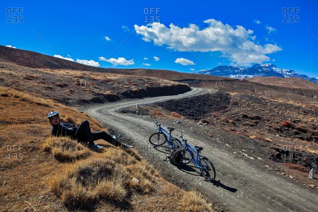 Himachal Pradesh, India - October 19, 2013: Biker resting on a roadside in Spiti valley of Himachal Pradesh, India