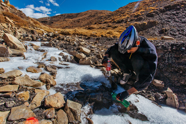 Himachal Pradesh, India - October 19, 2013: Cyclist filling up a bottle with water in Spiti valley of Himachal Pradesh, India