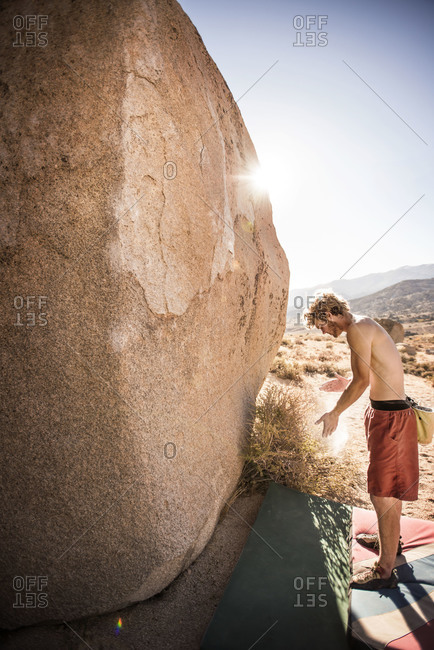 A young man puts chalk on his hands before attempting to climb a rock