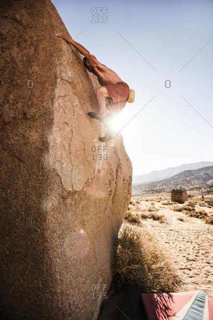 A young man climbs a desert rock