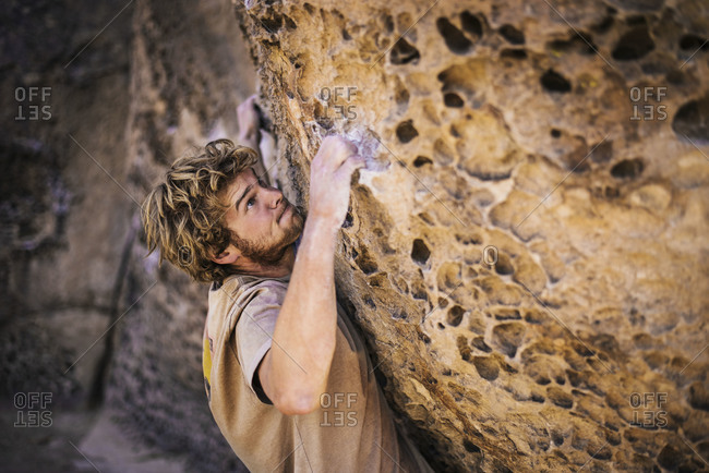 A rock climber with chalk on his hands struggles to pull himself up a rock