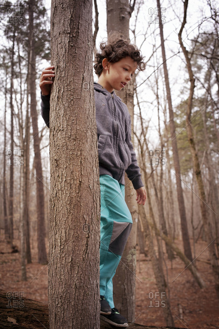 A boy walks on a log between two trees