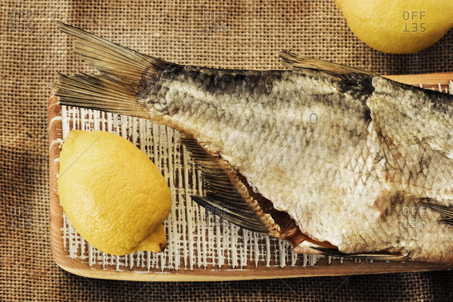 A whole cooked fish with a lemon