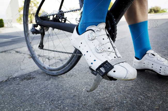A cyclist's shoe strapped to the bike pedal