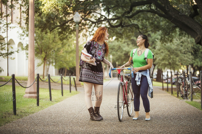 Two students laugh together on a college campus