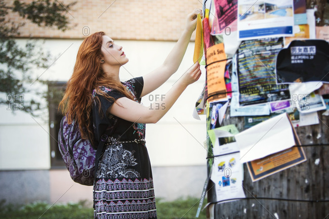 A young woman hands a flyer up on a post