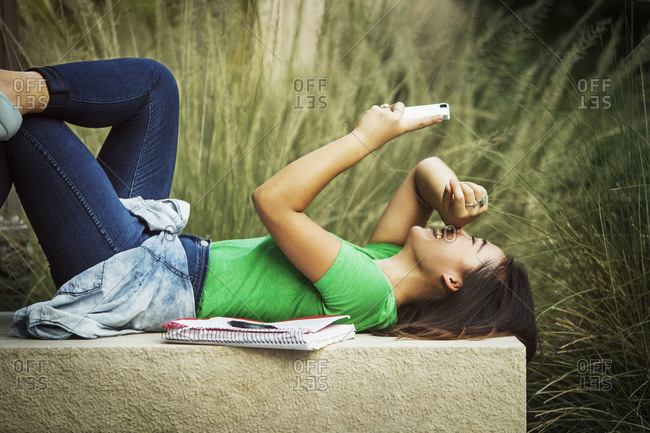 A college student laughs while looking at her phone on a bench