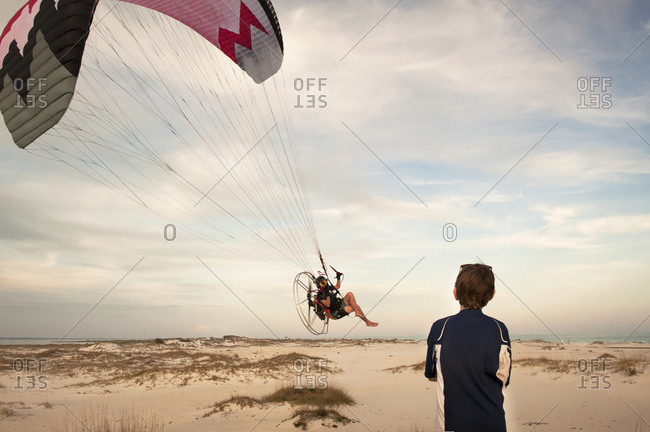 A boy watches a paramotorist land on the beach