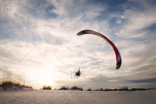 A man flies a powered paraglider over sand dunes at dusk
