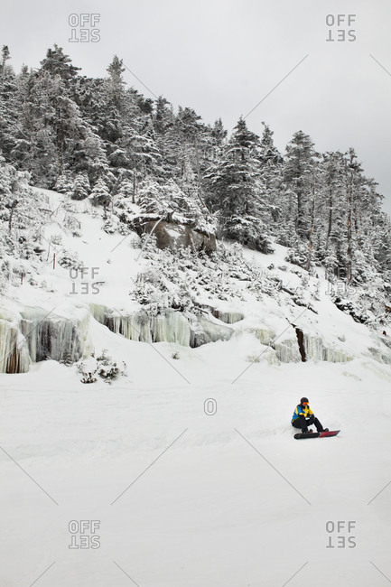 A snowboarder sits on the edge of a ski slope