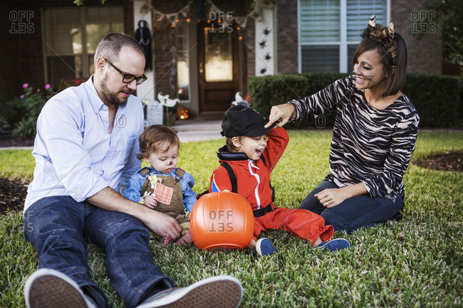 Family sitting in the grass in Halloween costumes
