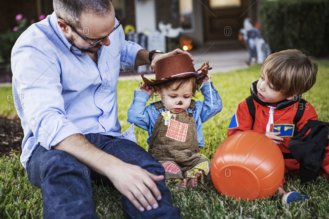 Father sitting in the grass with his sons in Halloween costumes