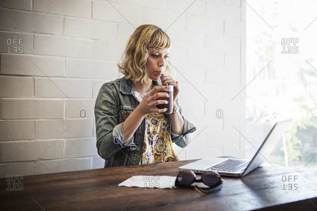 A woman sips iced tea and works on her computer