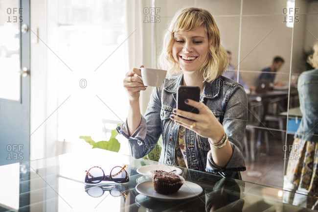 A woman smiles while checking her phone in a cafe