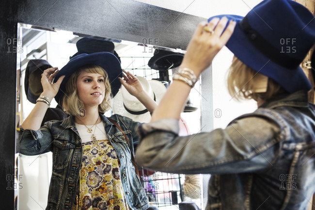 A young woman tries on a hat in a store
