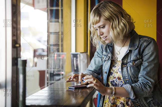 A woman types on her phone at a cafe