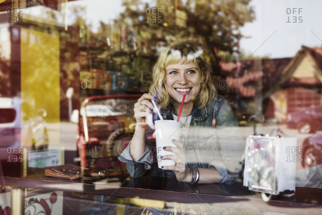 A woman smiles out the window of a restaurant as she drinks a milkshake