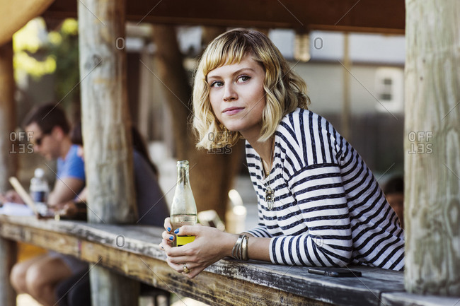 A woman leans over the a counter at an outdoor restaurant