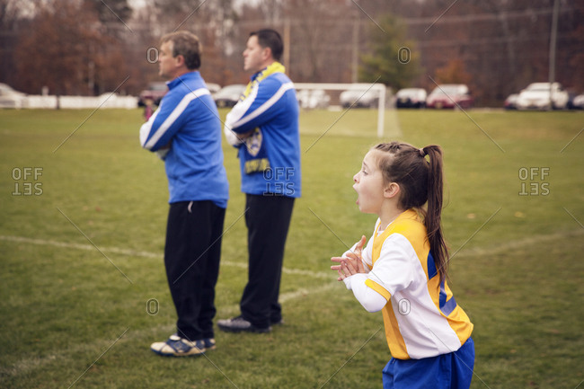 Girl cheering on team during soccer match