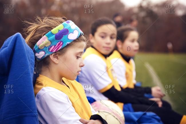 Girls sitting resting on soccer sideline