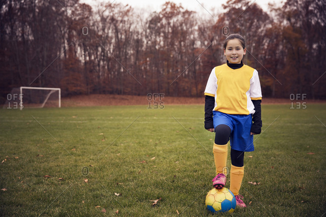 Girl with foot on soccer ball