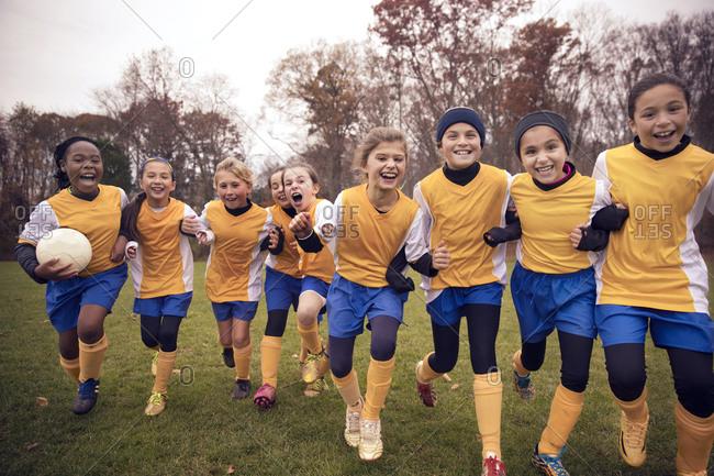Girls soccer team running together