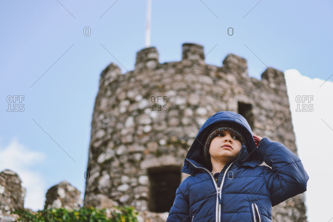 Boy standing in front of castle turret