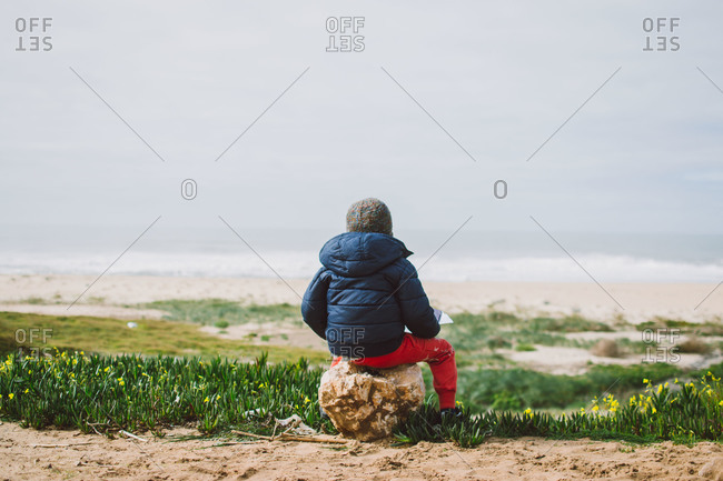 Child sitting on boulder looking at sea