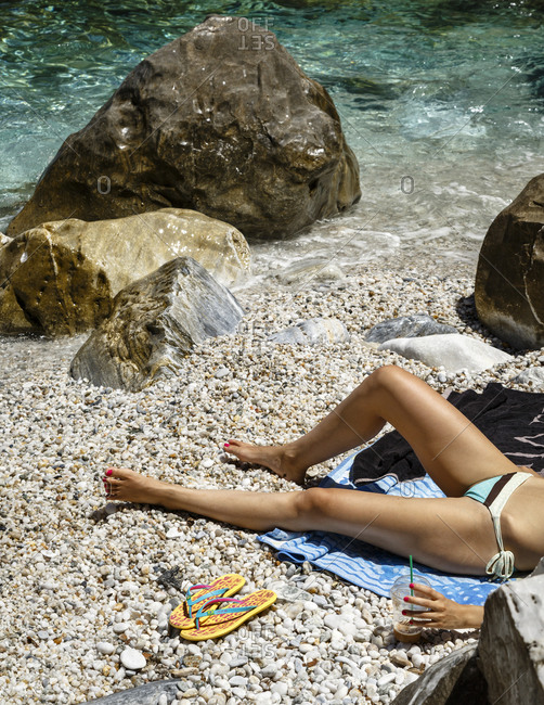Woman sunbathing at Fakistra beach in Pelion peninsula, Greece