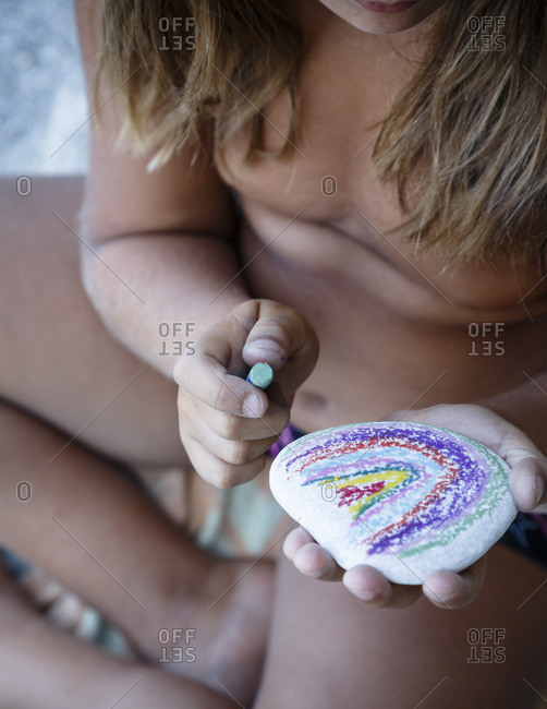 Kid painting on a sea pebble at Parisena beach in Horefto, Pelion peninsula, Greece