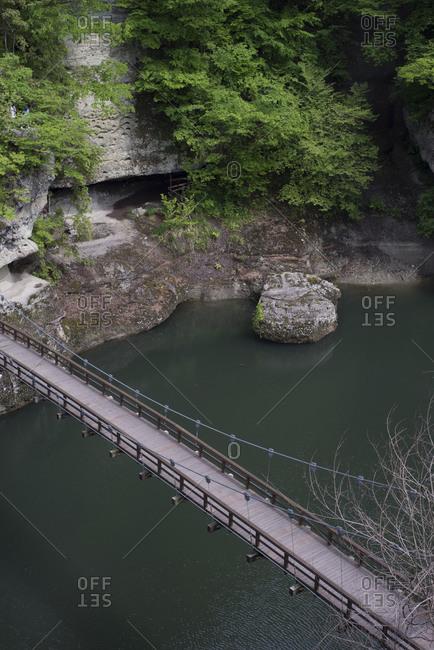 Footbridge over lush green river gorge, Tonohetsuri Gorge, Fukushima, Japan