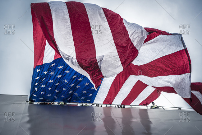 San Diego, CA, USA - May 21, 2015: Giant American flag hangs from a vessel during christening ceremony