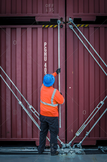 Port worker lashes containers together in San Diego CA USA