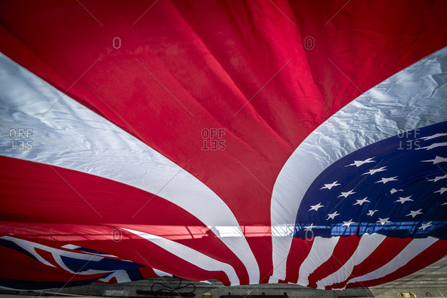 Giant American and Hawaiian state flag hanging from a ship for a christening ceremony in San Diego, CA