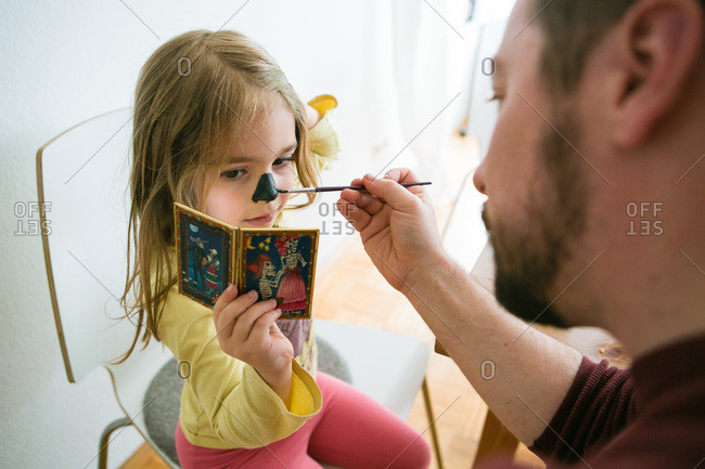 Man applying face painting on a nose of a girl