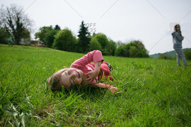 Young girl rolling in the grass