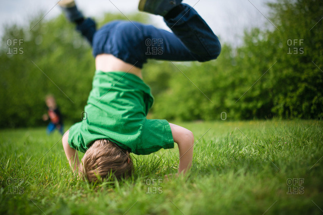 Young boy doing headstand in a park