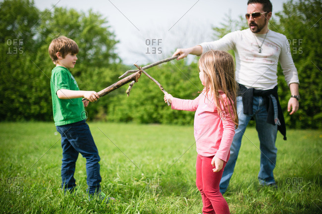 Father playing with his children in a park