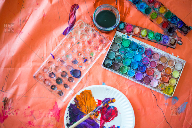 Overhead view of a drop cloth with artist's watercolors and brush