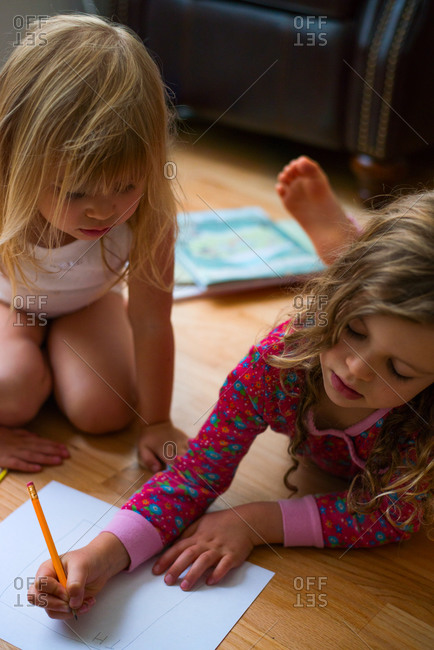 Young girl watches her sister write with a pencil on paper