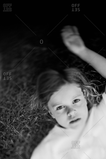 Overhead view of a young child lying on grass