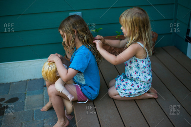 Young girl fixing her doll's hair as her sister plays with her hair