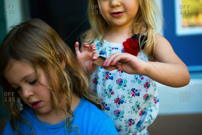 Young girl combing her sister's hair
