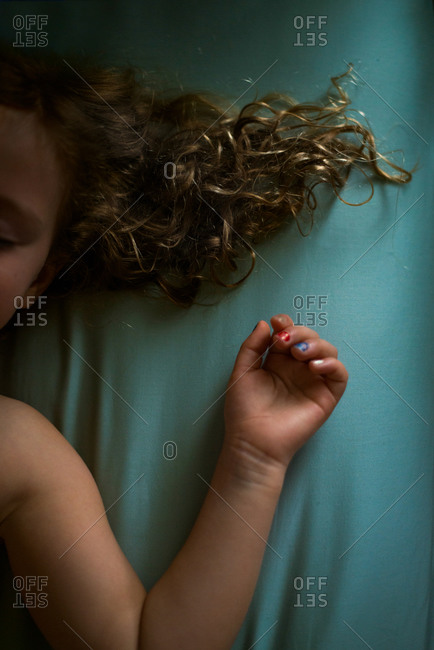 A sleeping child's arm and hair on a bed