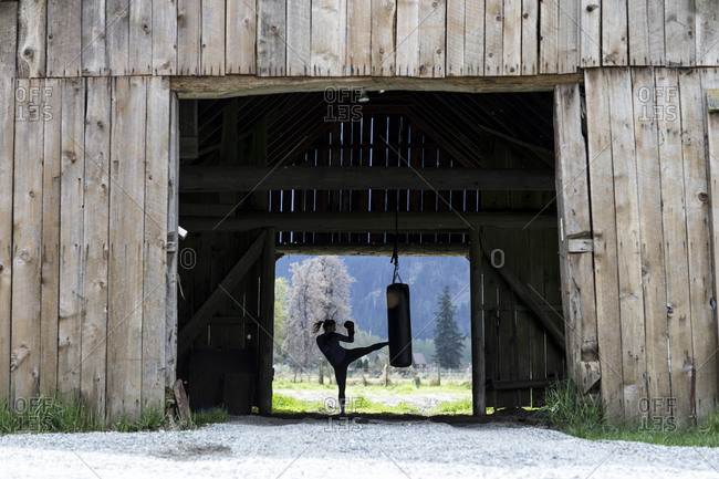 Young woman training in a barn