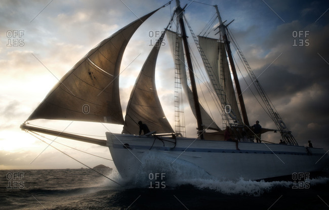 A large sailboat moving through the Caribbean Sea