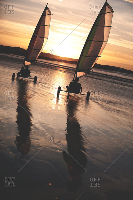 Two men sand yachting on the shore