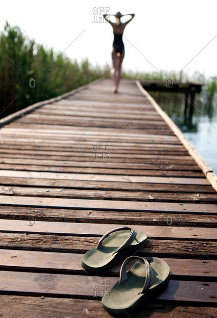 A woman walks down a pier leaving her flip flops behind